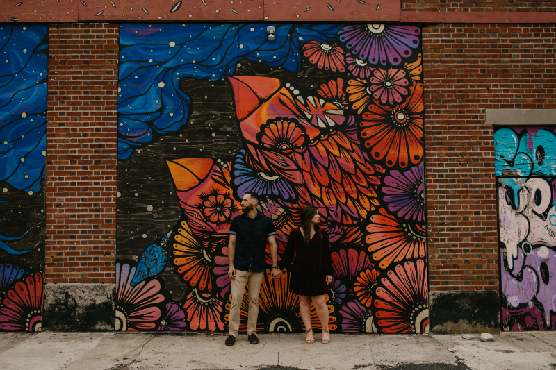Engagement photos in front of brightly colored mural