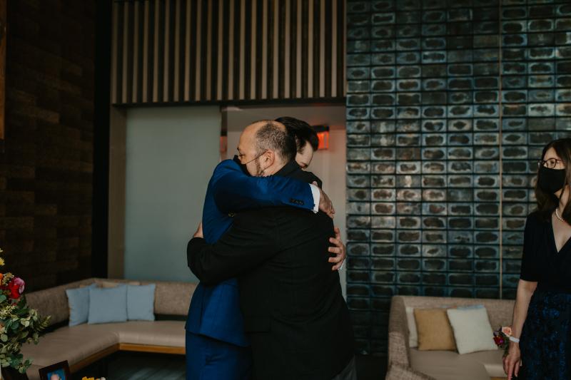 groom hugs dad before the wedding ceremony