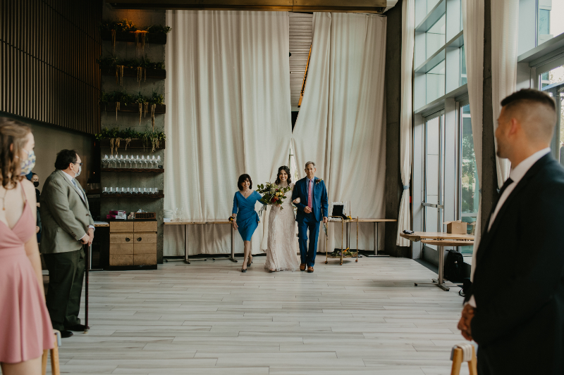 bride walks down the aisle with both parents