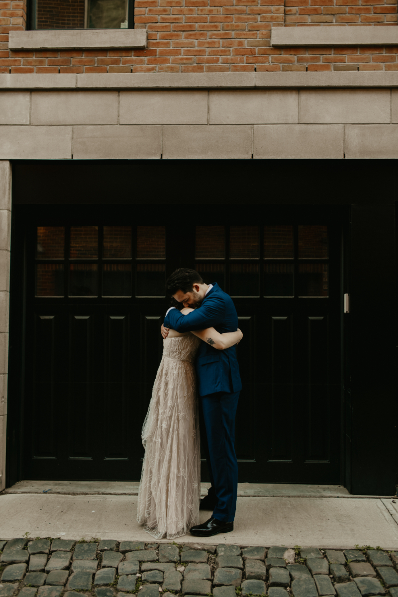 bride and groom embrace each other in Court Street, Hoboken, New Jersey