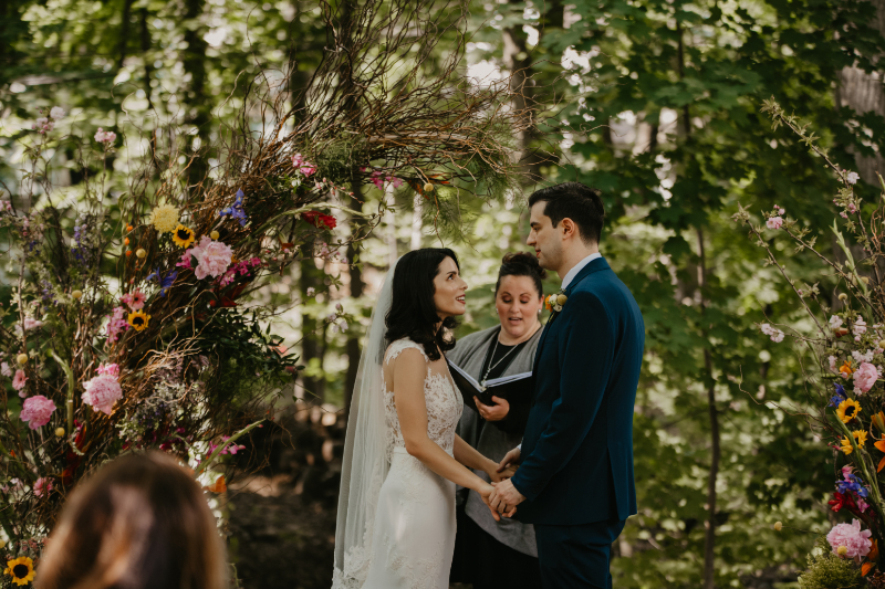 Outdoor wedding ceremony for home wedding with wildflower arch and forest backdrop