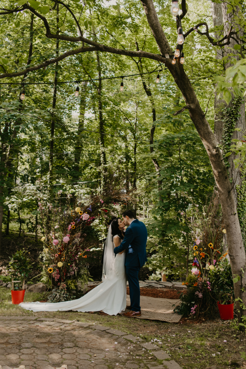 First kiss under wildflower arch at New Jersey home wedding