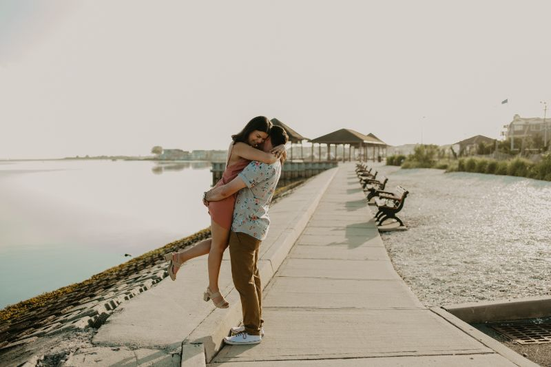Holding each other close with this Boardwalk Beach Photoshoot at Long Beach Island. Engagement Photos of a young couple loving life.