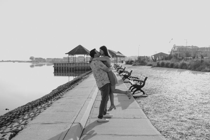 Beach Engagement Photoshoot in Black and White on the Boardwalk. This Couple is walking on clouds, in this stunningly beautiful Professional Picture.