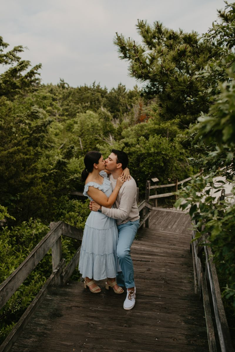 Engagement photos in a green forest on a rustic wooden walkway. Beautiful Couples Photoshoot in Long Beach Island.