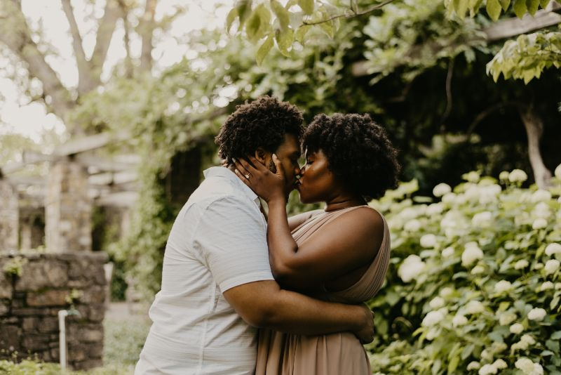 Head over heels in love, kissing at the Cross Estate Gardens for Engagement Photos.