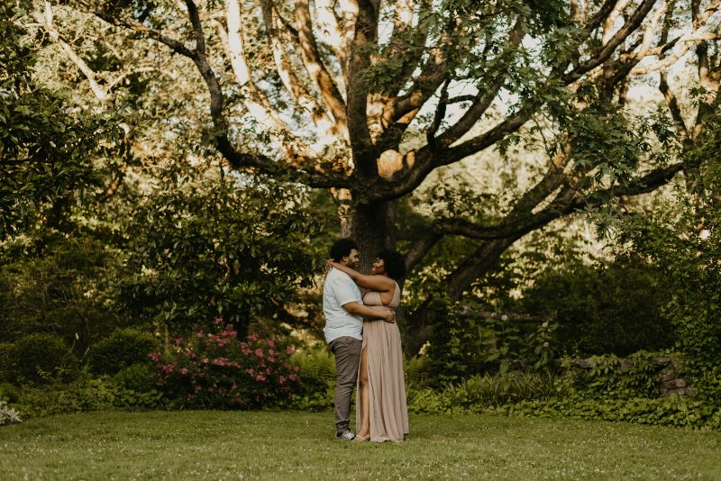 Standing at the base of a giant tree at Cross Estate Gardens for Engagement Photos.