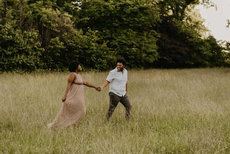 A future husband leading his future bride across a field in Cross Estate Gardens. Stunning Engagement Photoshoot with a professional photographer.